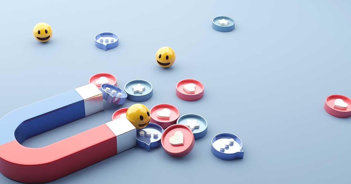 Μαγνήτης προσελκύει χαμογελαστά emoji και καρδούλες. Συμβολισμός για την αποτελεσματική διαφήμιση στα social media